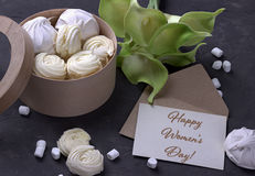 Bouquet of green yellow callas with marshmallows in a wooden round box on a gray wooden background and lettering happy women`s day Stock Images