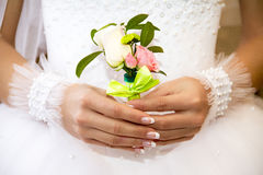 Bouquet for the groom. The bride holding a bouquet for the groom Stock Photo