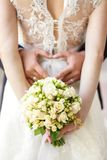 Young bride in a beautiful dress holding a bouquet in hands royalty free stock images