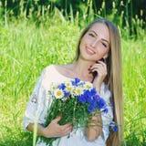 Bouquet heureux d'esprit de femme des camomilles et des bleuets photographie stock libre de droits