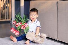 Bouquet heureux mignon de participation de petit garçon des tulipes rouges et l'ours de nounours mol se reposant sur la mère de s images libres de droits