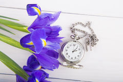 Bouquet of irises with alarm clock on white wooden background Royalty Free Stock Photography