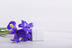 Bouquet of irises with gift box on white wooden background Stock Photo