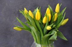 Bouquet jaune élégant de tulipes sur le gris Images stock
