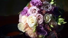 Bouquet l'épousant en gros plan et beau de laiterie de roses, blanc et lilas Dans la densité jeu de la lumière et des ombres banque de vidéos