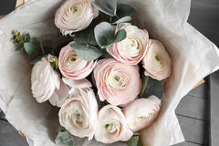 Bouquet of light pink ranunculus in vase on wooden background Royalty Free Stock Photo