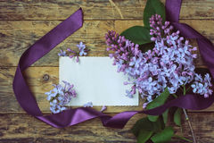 Bouquet lilac branches and blank greeting card. Bouquet lilac branches with purple ribbon and blank greeting card on old wooden table Royalty Free Stock Photography