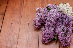 Bouquet of lilac on brown wooden background stock photography