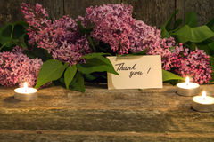 Bouquet of lilac, candle and thank you card on old wooden backgr. Composition of a bouquet of lilac, candle and thank you card on old wooden background closeup Royalty Free Stock Photos