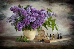 Bouquet of lilac and chess. Bouquet of lilac, chess and clock stock photo