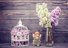 Bouquet lilac flowers, angel and bird cage. style nostalgia Stock Photography