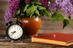 Bouquet of lilac flowers in a ceramic pot with a black alarm clock Stock Photos