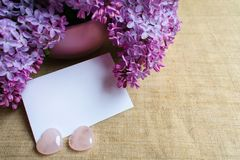 A bouquet of lilac flowers in a lilac vase and an envelope. Copy space stock photography