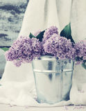 Bouquet of lilac flowers in a metal bucket an old wooden board, a decor in vintage style. Spring romantic bouquet for your holiday Royalty Free Stock Photo