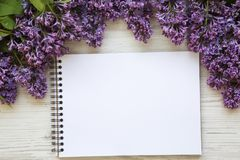 A bouquet of lilac flowers with notebook on a white wooden background. Copy space. Mothers Day. Top view. stock photos