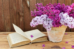 Bouquet of lilac flowers in a pot and old book on a background o. F vintage wooden board. Home decor in a rustic style Stock Image