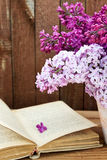 Bouquet of lilac flowers in a pot and old book on a background o. F vintage wooden board. Home decor in a rustic style Royalty Free Stock Photography