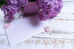 A bouquet of lilac flowers in a lilac vase and an envelope. Copy space royalty free stock photo