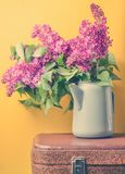 Bouquet of lilac in an old enameled teapot on vintage suitcase on yellow background. Retro style still life. Bouquet of lilac in an old enameled teapot on stock photo