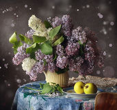 Bouquet of a lilac. Still life with a bouquet of a lilac and apples Royalty Free Stock Photo