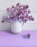 Bouquet of lilac in a vase on a wooden background, spring Stock Image