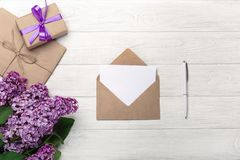 A bouquet of lilacs with craft envelope, gift box, a love note on white boards royalty free stock image