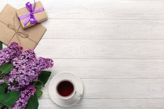 A bouquet of lilacs with cup of tea, gift box, craft envelopes, a love note on white boards stock photo