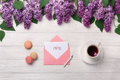 A bouquet of lilacs, cup of tea, love note and macarons on a white wooden table royalty free stock photos