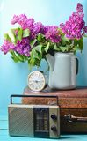 Bouquet of lilacs in enameled kettle on antique suitcase, vintage radio, alarm clock on blue background. Retro style still life. Bouquet of lilacs in enameled royalty free stock image