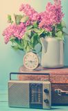 Bouquet of lilacs in enameled kettle on antique suitcase, vintage radio, alarm clock on blue background. Retro style still life. Bouquet of lilacs in enameled stock photography