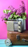 Bouquet of lilacs in enameled kettle on antique suitcase, vintage radio, alarm clock on pink background. Retro style still life. Bouquet of lilacs in enameled royalty free stock photos