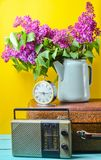 Bouquet of lilacs in enameled kettle on antique suitcase, vintage radio, alarm clock on yellow background. Retro style still life. Bouquet of lilacs in enameled royalty free stock image