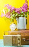 Bouquet of lilacs in enameled kettle on antique suitcase, vintage radio, alarm clock on yellow background. Retro style still life. Bouquet of lilacs in enameled stock photography
