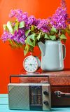 Bouquet of lilacs in enameled kettle on antique suitcase, vintage radio, alarm clock on yellow background. Retro style still life. Bouquet of lilacs in enameled royalty free stock photography