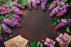 A bouquet of lilacs with gift box, craft envelope on rusty background . Mother`s day stock photography