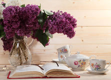 Bouquet of lilacs, open book, spectacles, teapot and cup of tea Stock Image