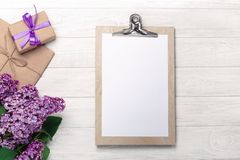 A bouquet of lilacs with tablet, gift box and craft envelope on white boards stock images