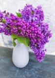 Bouquet of lilacs  a vase on retro concrete vintage background stock image