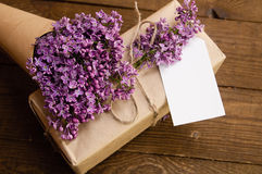 Bouquet of lilacs on a wooden table with a gift box stock photos