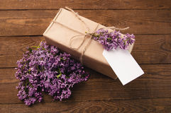 Bouquet of lilacs on a wooden table with a gift box royalty free stock photo