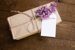 Bouquet of lilacs on a wooden table with a gift box royalty free stock images