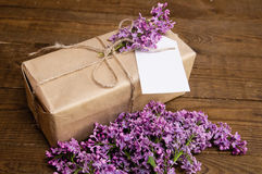 Bouquet of lilacs on a wooden table with a gift box Royalty Free Stock Photos