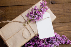 Bouquet of lilacs on a wooden table with a gift box Royalty Free Stock Image