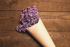 A bouquet of lilacs on a wooden table royalty free stock images