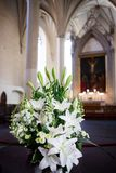 Bouquet of lilies and snapdragons in church. A large bouquet of white lilies and snapdragons at the altar of a church Stock Photography