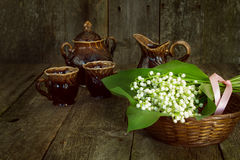 Bouquet of lilies of the valley in a basket with cups and sugar Royalty Free Stock Photos