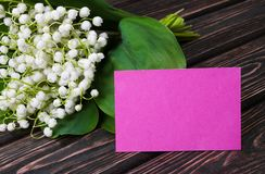 Bouquet lily of the valley. And blank paper on wood desk. Mothers day Stock Photos