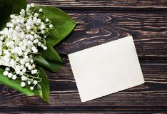 Bouquet lily of the valley. And blank paper on wood desk. Mothers day Royalty Free Stock Image