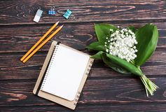 Bouquet lily of the valley. And blank paper on wood desk. Mothers day Stock Photo
