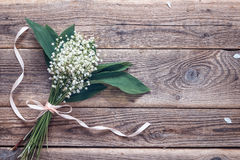 Bouquet of lily of the valley on the old wooden background. Plac. E for text. Top view Royalty Free Stock Photos
